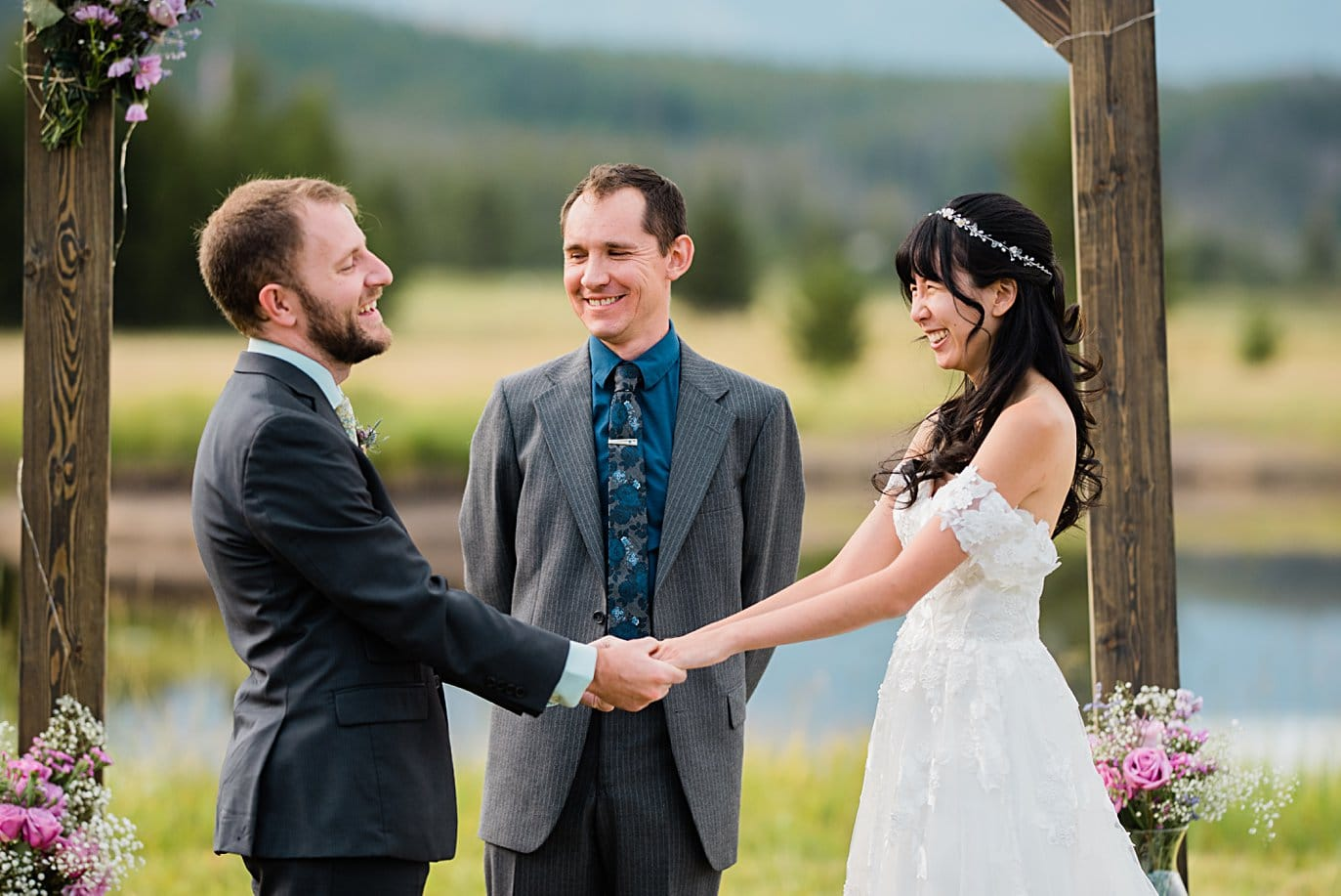 bride and groom laugh during vows at intimate Grand Lake wedding by Denver wedding photographer Jennie Crate