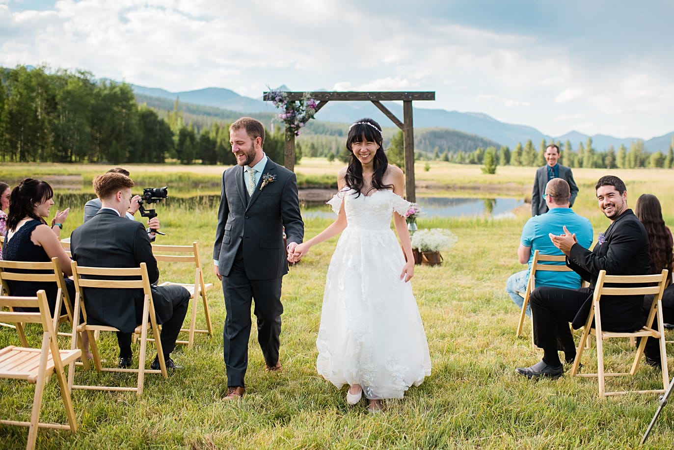 bride and groom walk back won aisle after outdoor Colorado ceremony at intimate Grand Lake wedding by Estes Park wedding photographer Jennie Crate