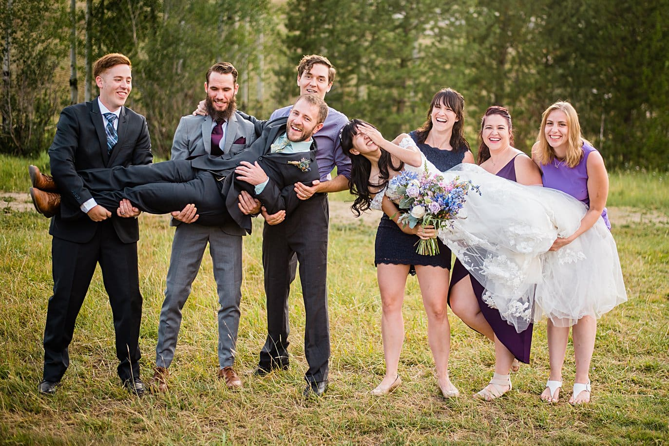 friends lift bride and groom after outdoor Colorado mountain ceremony at intimate Grand Lake wedding by Estes Park wedding photographer Jennie Crate