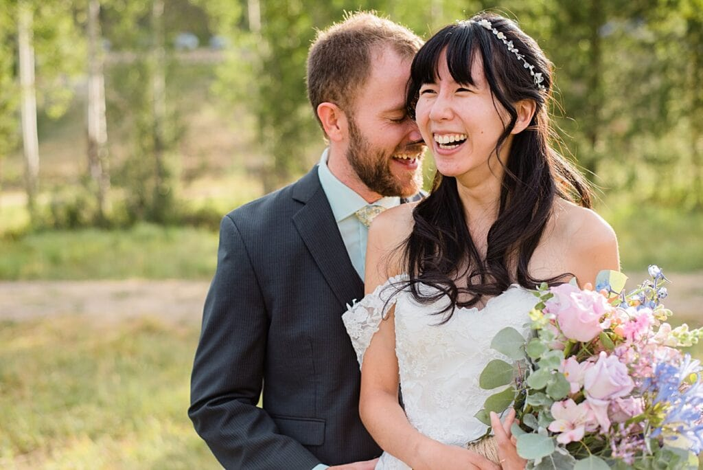 bride and groom laughing at intimate Grand Lake wedding by Estes Park wedding photographer Jennie Crate