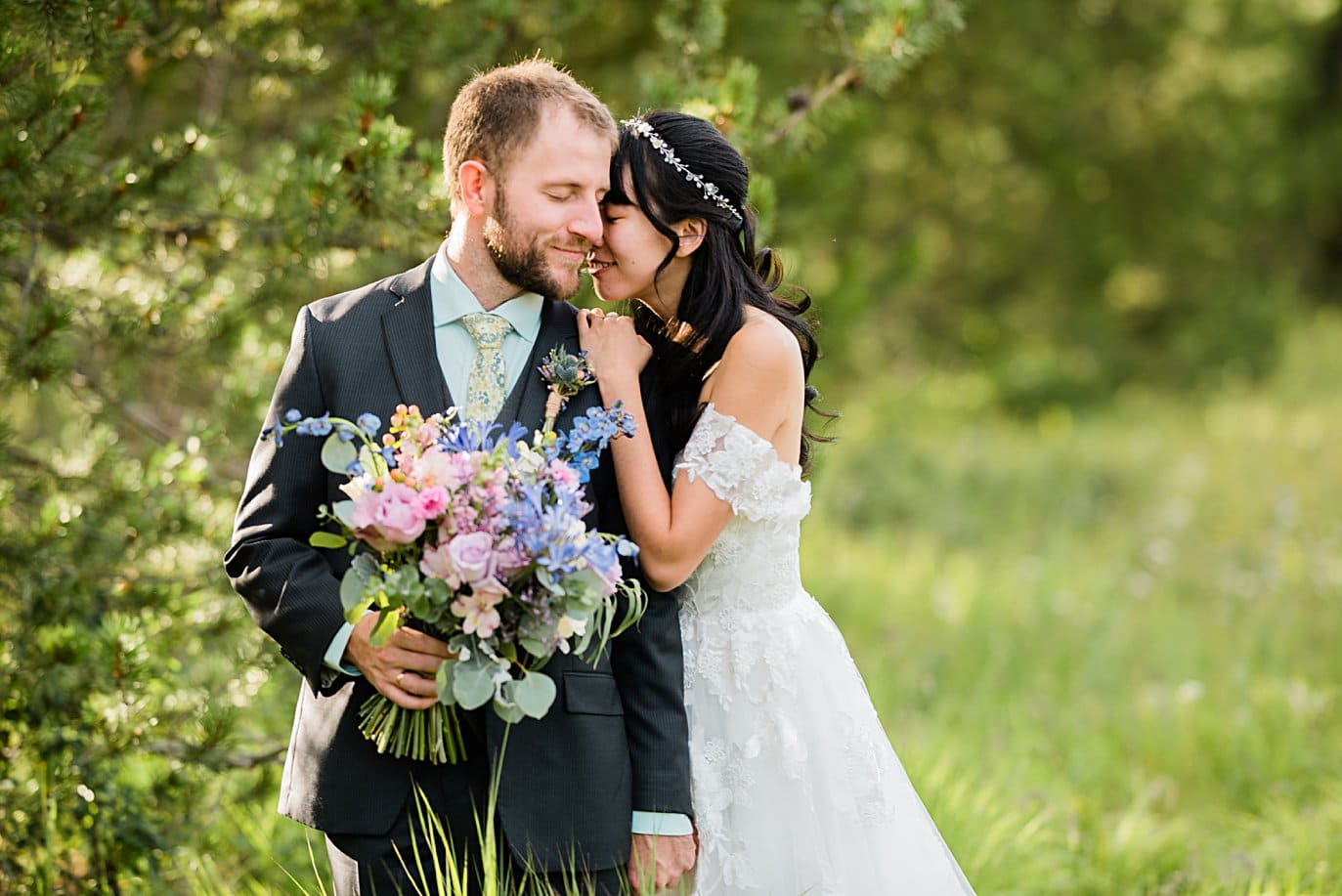 bride and groom with wildflower bouquet at intimate Grand Lake wedding by Estes Park wedding photographer Jennie Crate