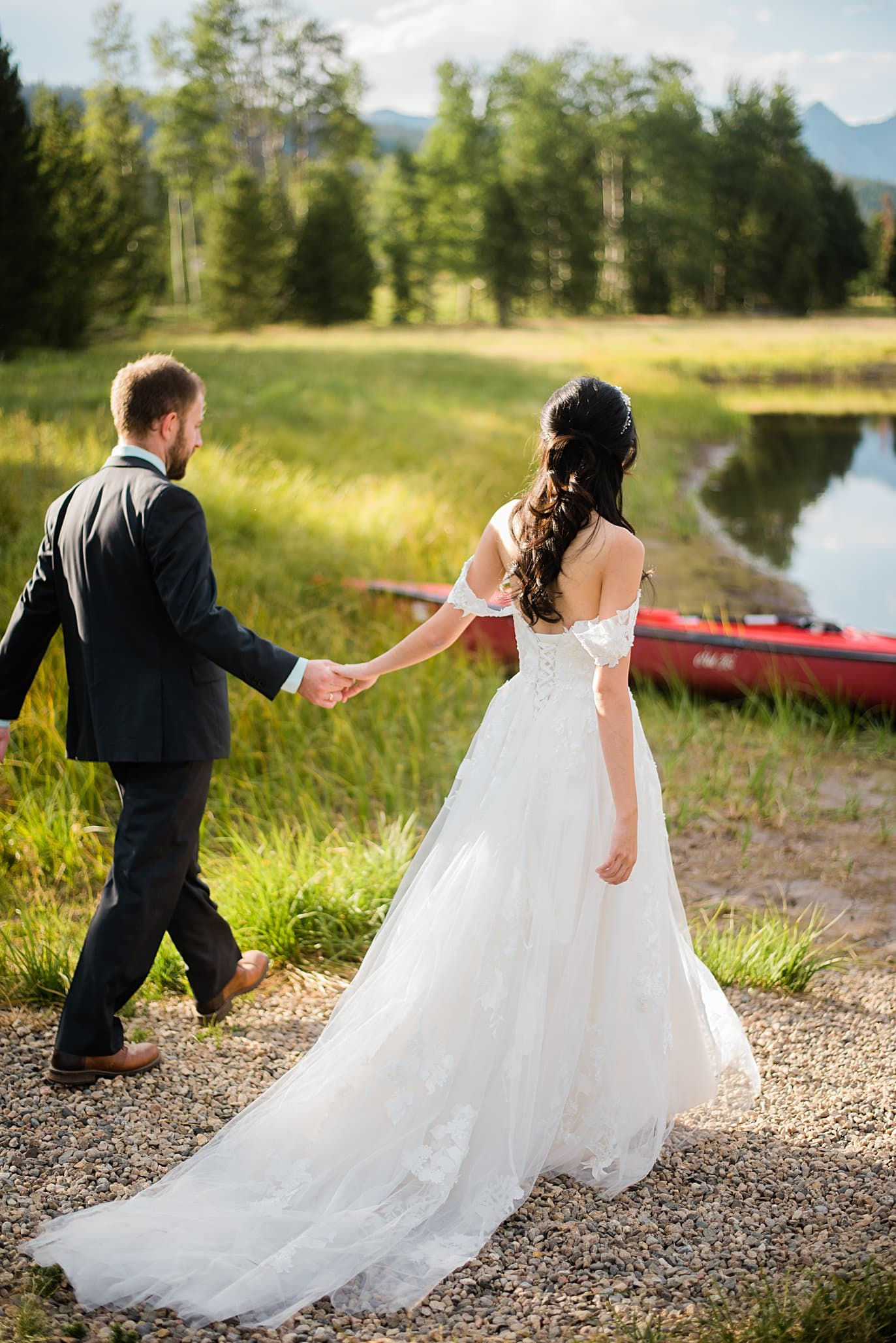 bride and groom walk hand in hand to pond and canoe after at intimate Grand Lake wedding by Boulder wedding photographer Jennie Crate