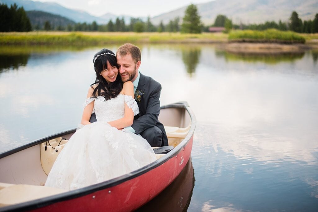bride and groom in canoe after Colorado wedding ceremony at intimate Grand Lake wedding by Boulder wedding photographer Jennie Crate
