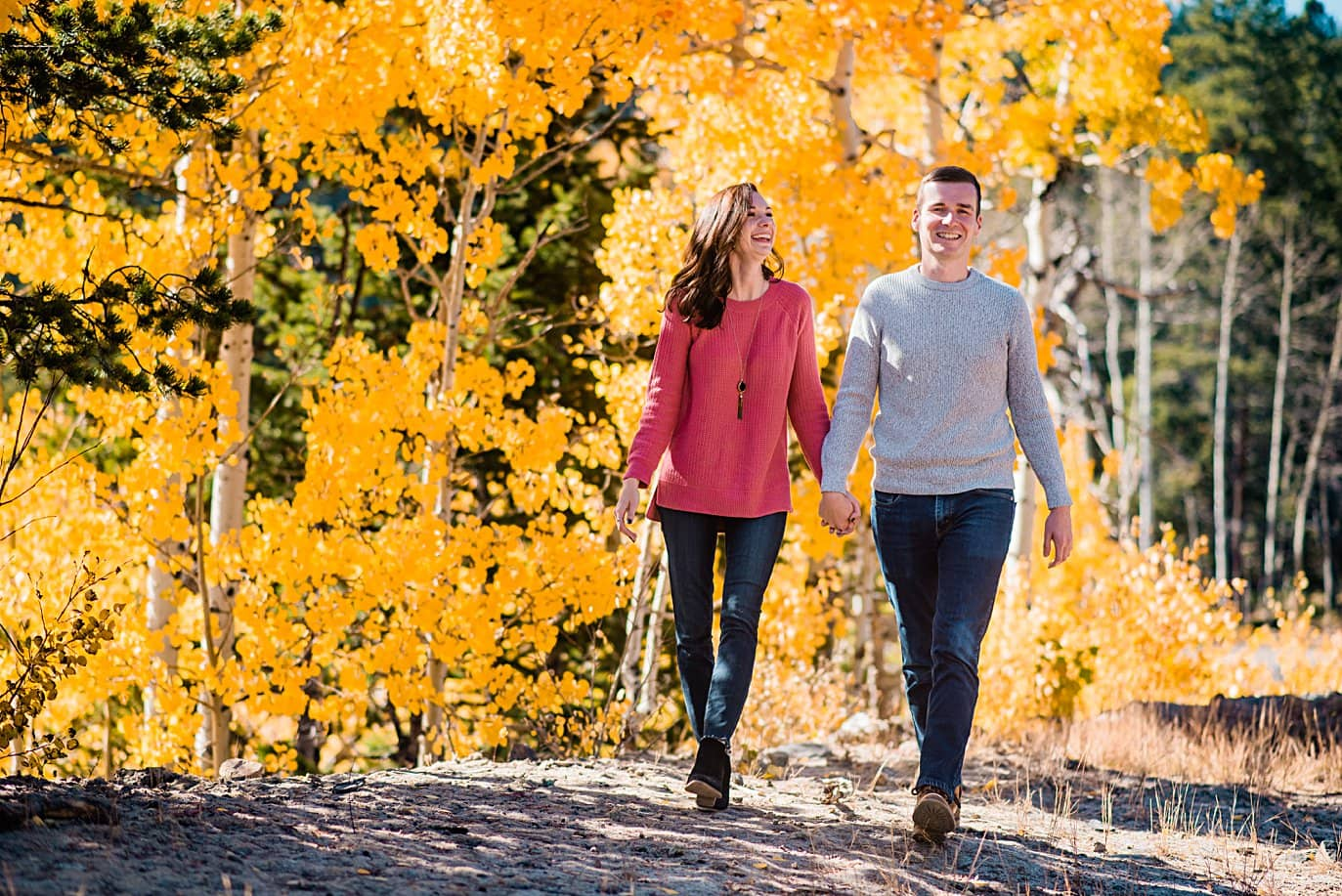couple walks hand in hand in front of yellow aspens during fall engagement session in Ward Colorado by Boulder engagement photographer Jennie Crate
