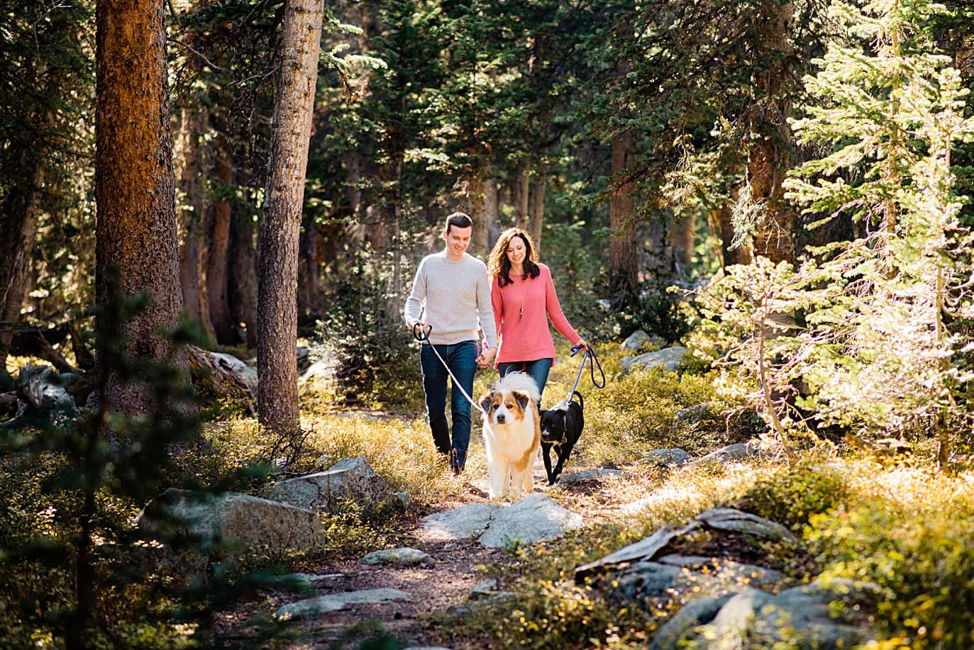 couple walks through woods on hike Mitchell Lake engagement session by Boulder engagement photographer Jennie Crate
