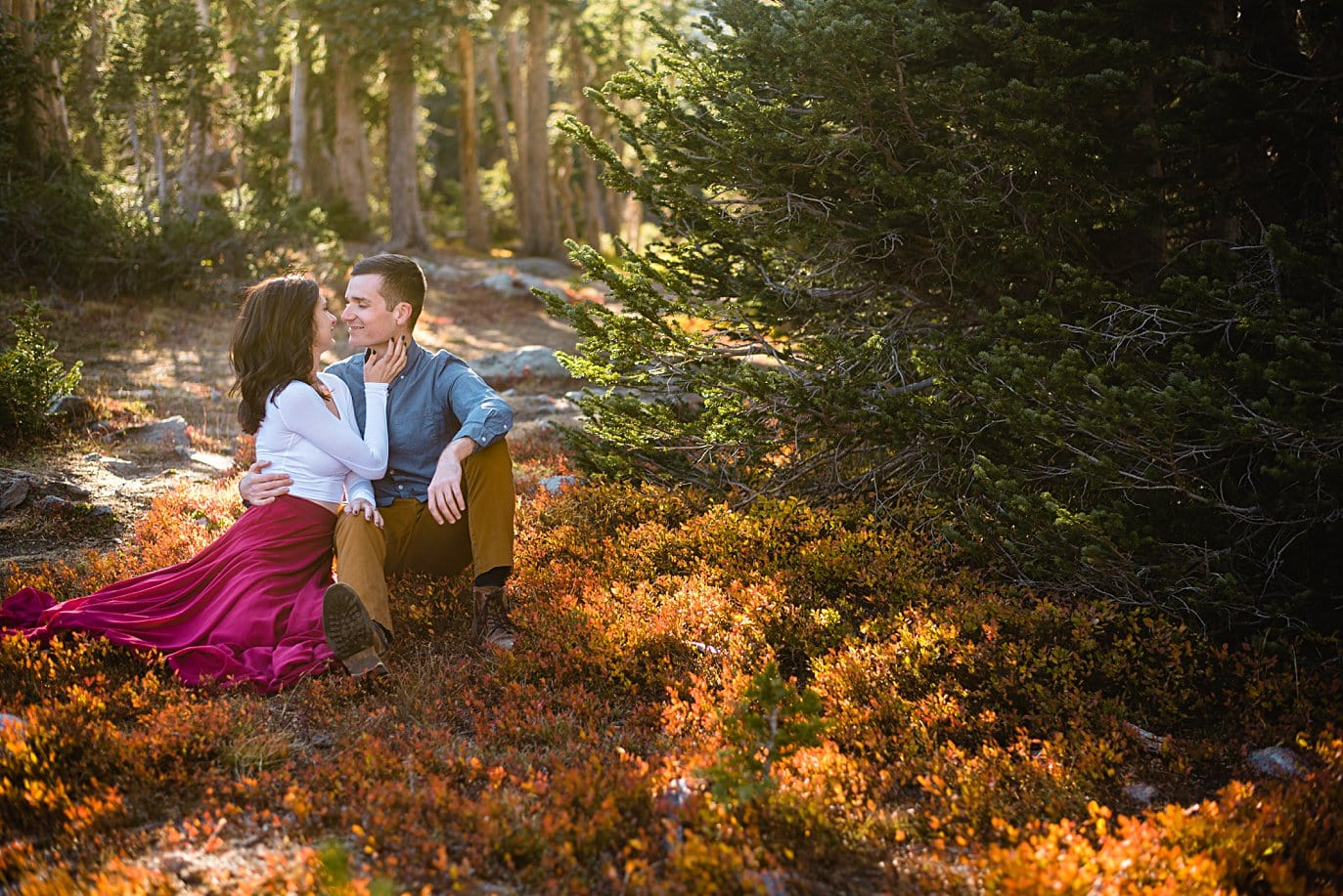 couple cuddles in orange fall foliage during fall engagement hike by Boulder engagement photographer Jennie Crate