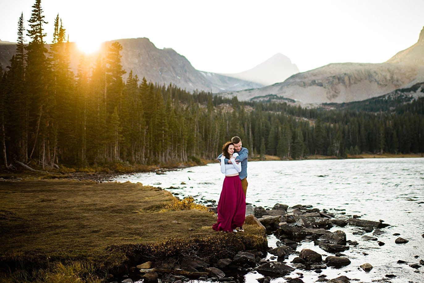 sunset engagement at Mitchell Lake as sun peeps over peaks with couple in colorful attire by Denver engagement photographer Jennie Crate
