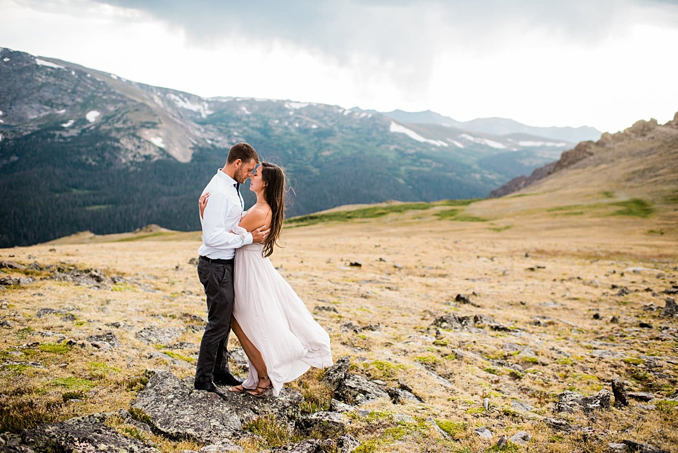 couple perched on rock summer trail ridge road engagement session by RMNP engagement photographer Jennie Crate