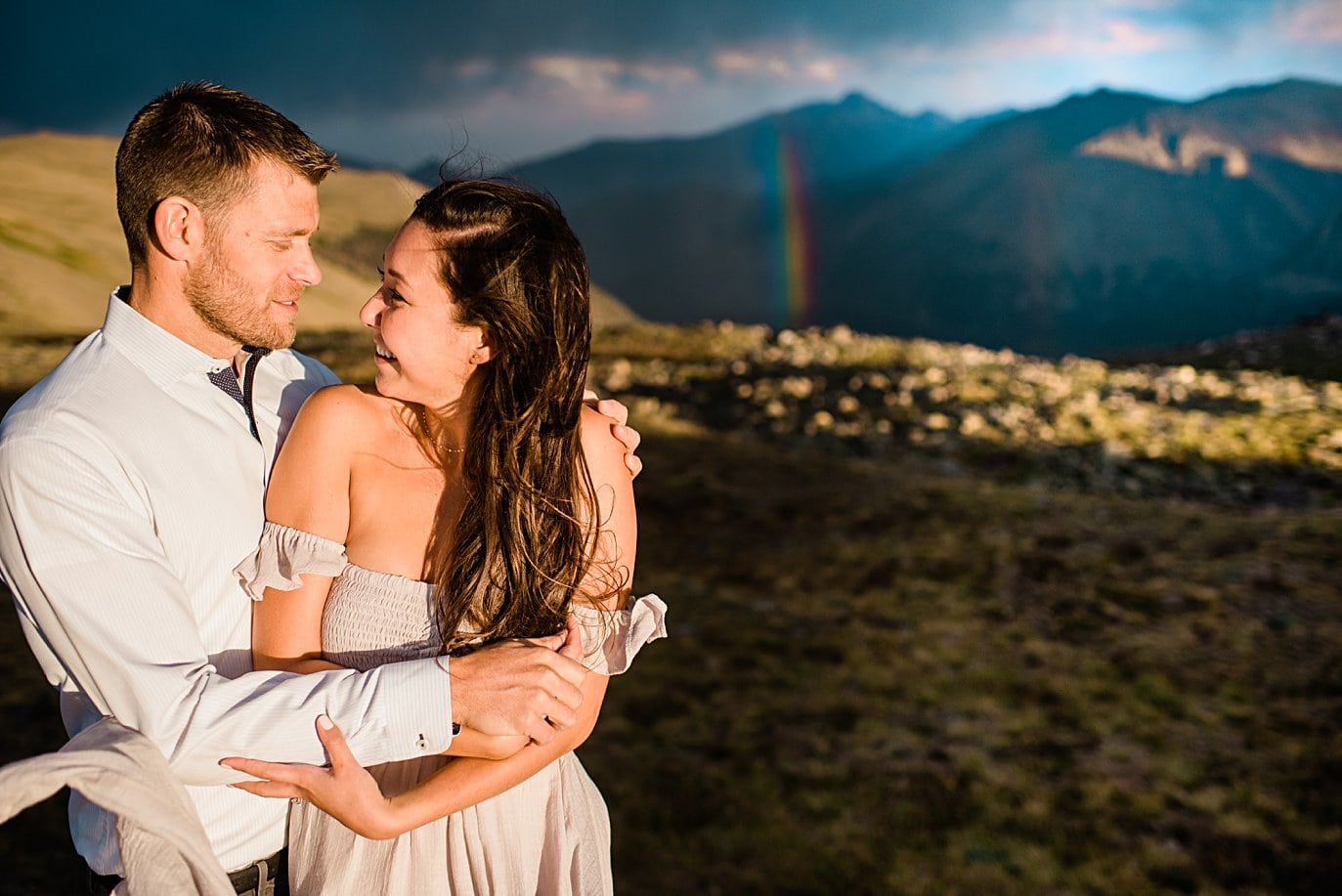 bride and groom in boho attire with rainbow at top of trail ridge road during engagement session by Estes Park engagement photographer Jennie Crate