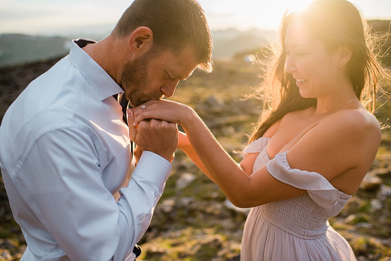 groom kisses fiance's hand at sunset at top of trail ridge road during engagement session by Estes Park engagement photographer Jennie Crate