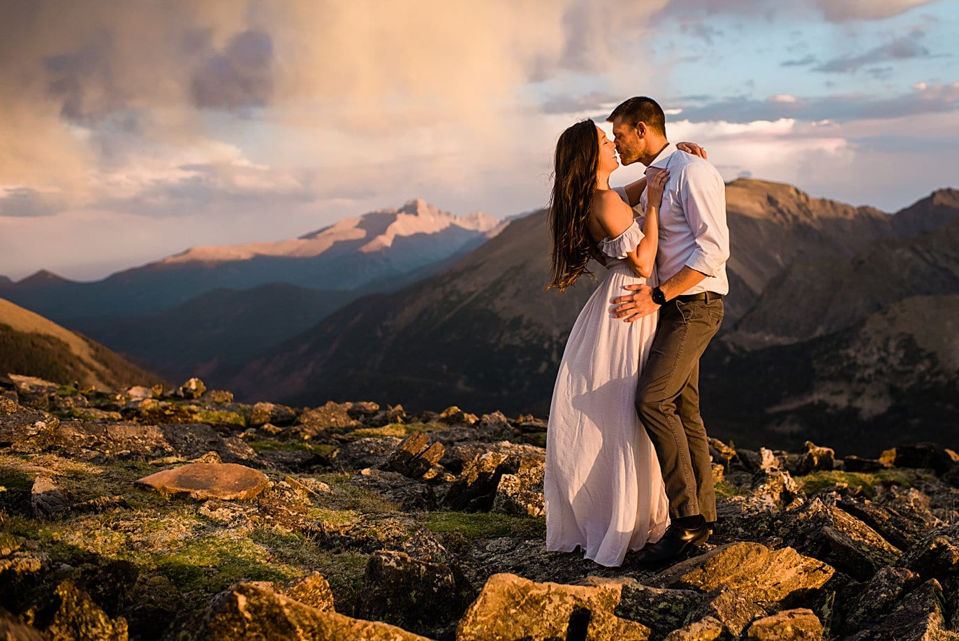 bride and groom embrace on rocks at top of trail ridge road during engagement session by Estes Park engagement photographer Jennie Crate