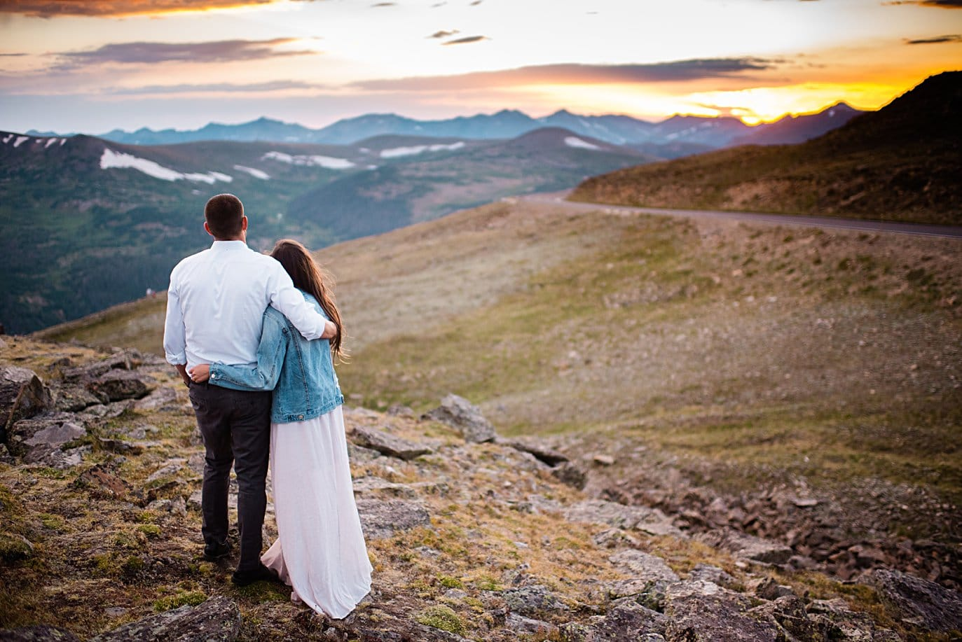 engaged couple take in sunset at top of trail ridge road during engagement session by Estes Park engagement photographer Jennie Crate