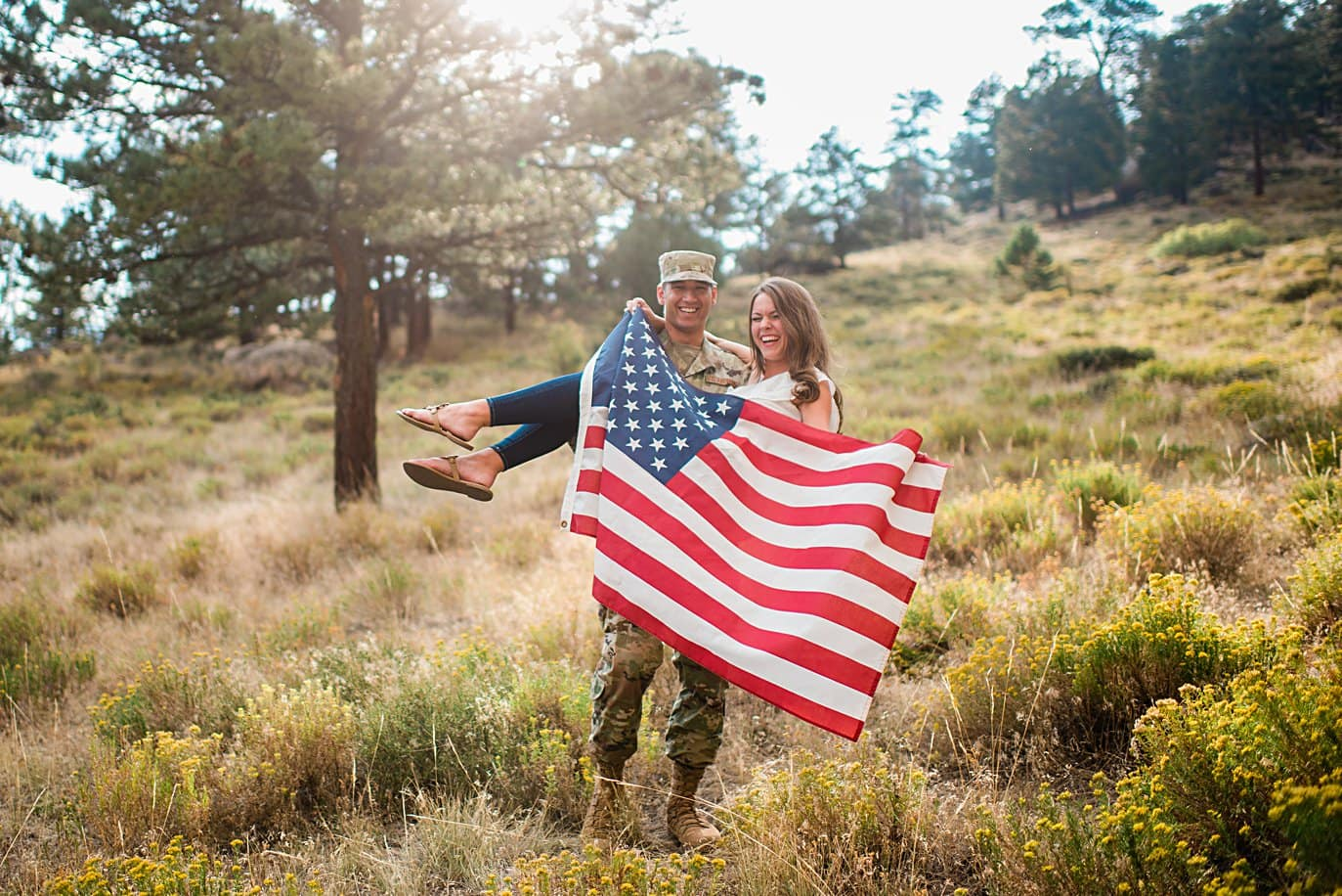 engaged couple with military uniform and American flag at Rocky Mountain National Park engagement by Estes Park engagement photographer Jennie Crate