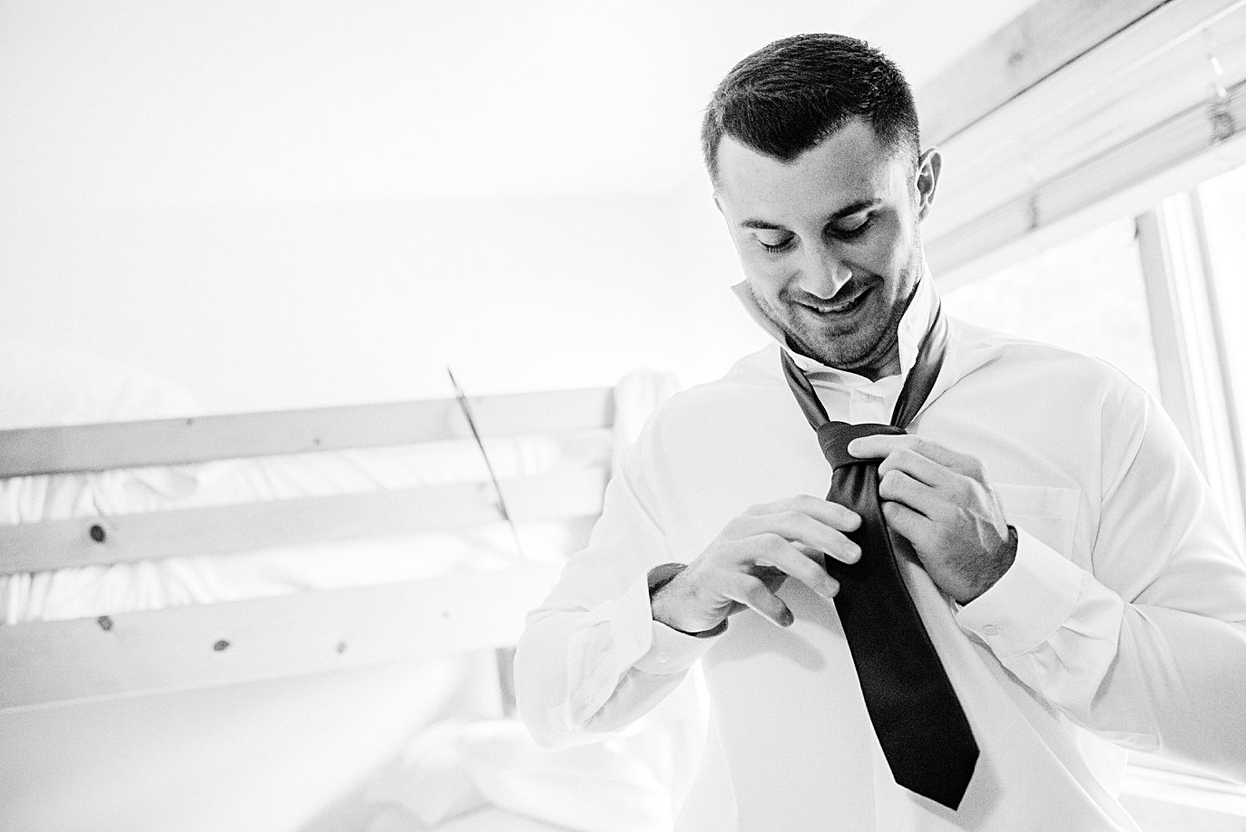 groom ties tie on wedding day at Larkspur Vail Wedding by Vail Wedding photographer Jennie Crate