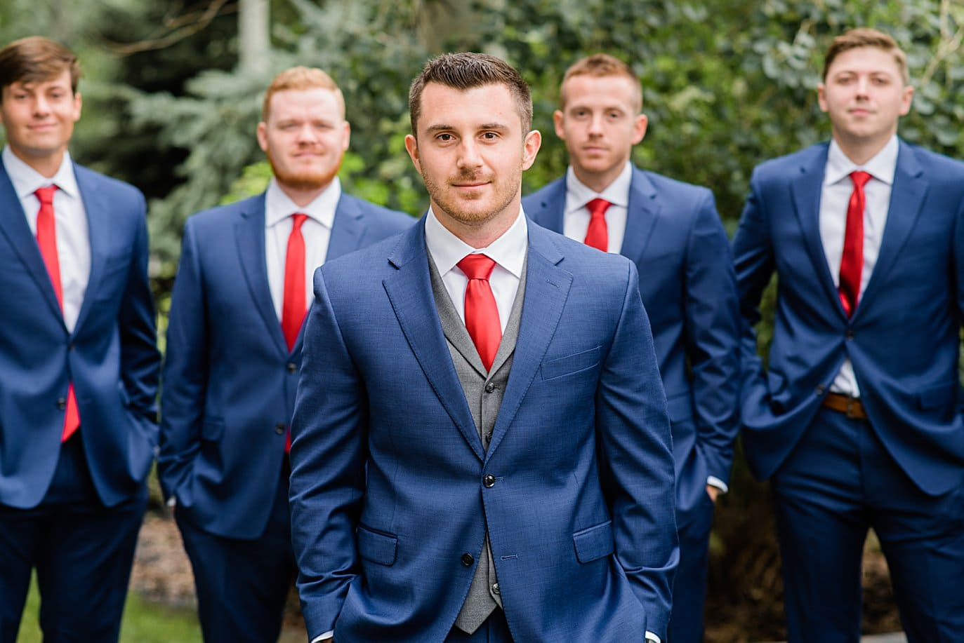 groom and groomsmen in navy suits and red ties at Larkspur Vail Wedding by Vail Wedding photographer Jennie Crate