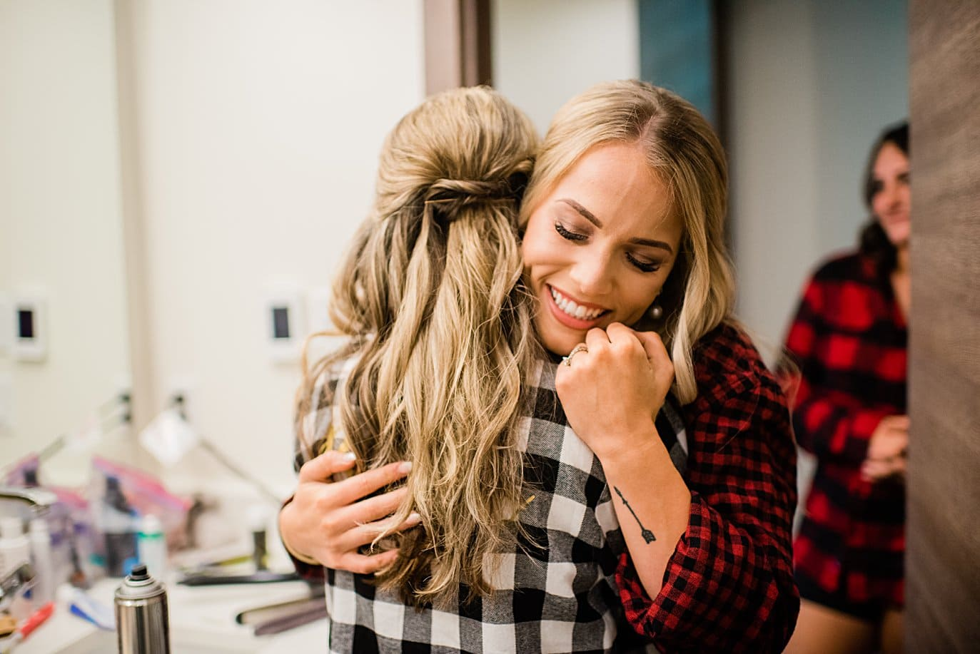 bride hugging bridesmaid in flannel shirts at Larkspur Vail Wedding by Vail Wedding photographer Jennie Crate