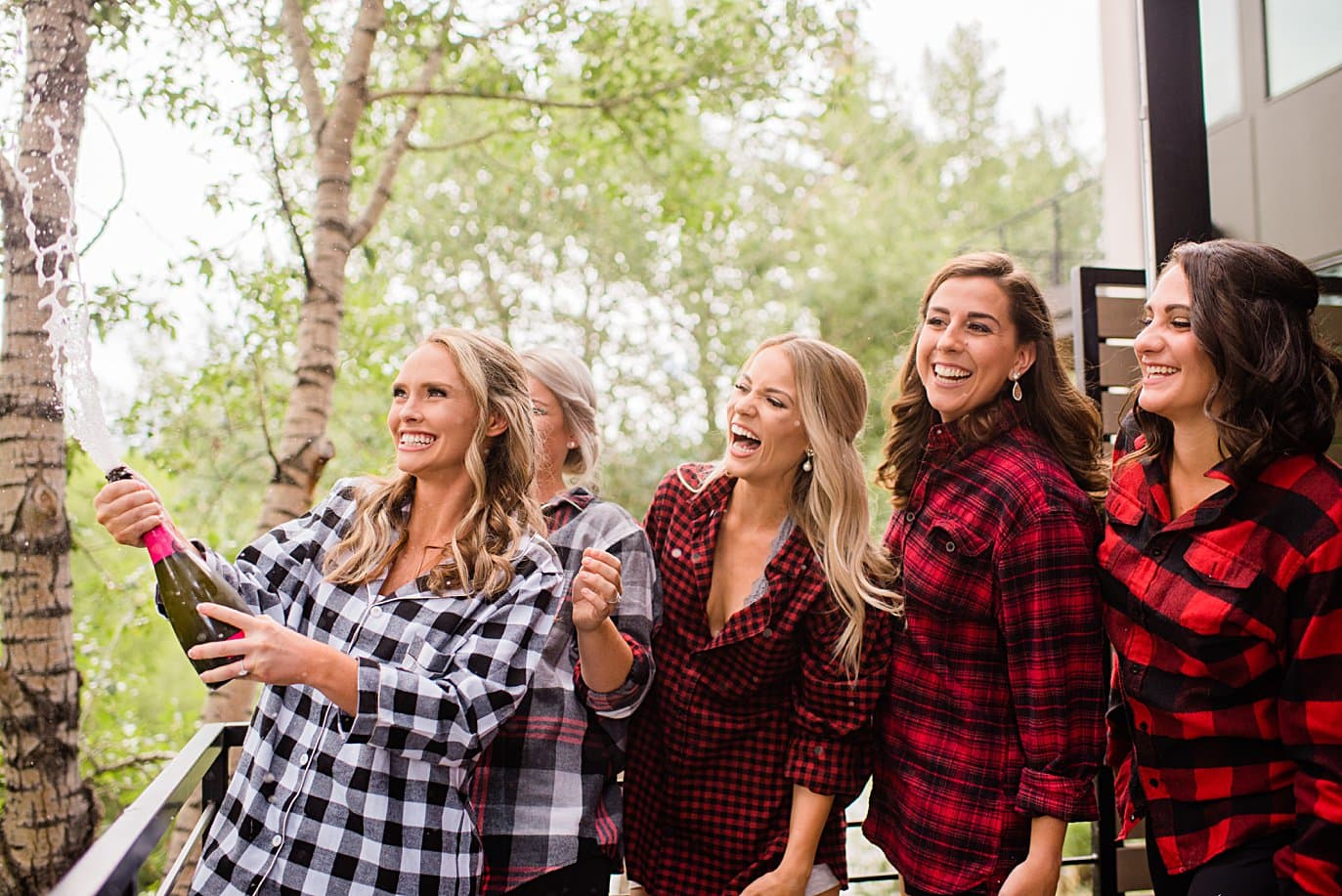 bride and bridesmaids in plaid shirts popping champagne while getting ready at Larkspur Vail Wedding by Vail Wedding photographer Jennie Crate