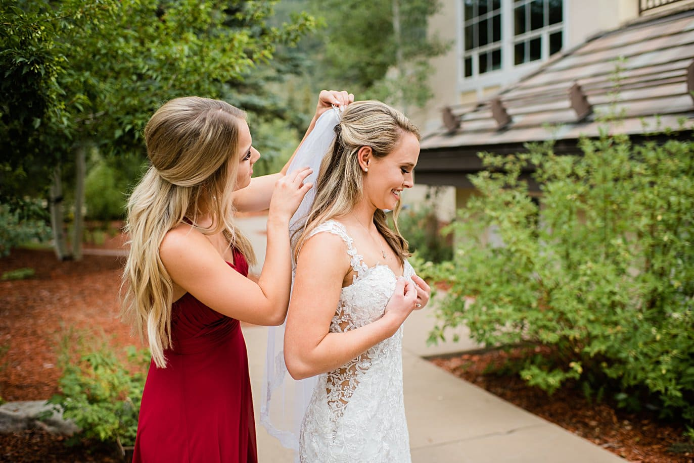 bridesmaid puts vail on bride at Larkspur Vail Wedding by Vail Wedding photographer Jennie Crate