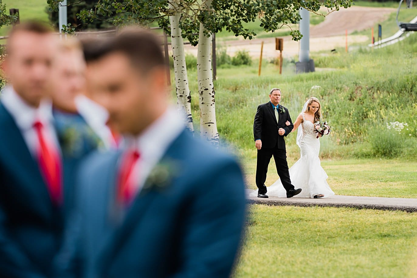 bride and father approach wedding ceremony at Larkspur Vail Wedding by Lyons Wedding photographer Jennie Crate