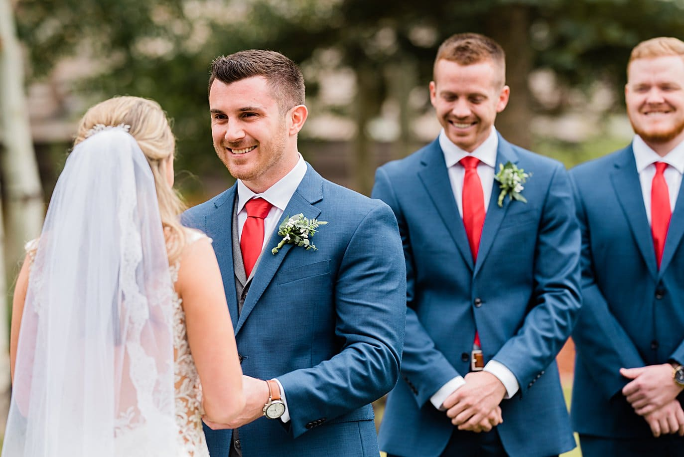 groom smiles at bride during outdoor mountain ceremony at Larkspur Vail Wedding by Lyons Wedding photographer Jennie Crate