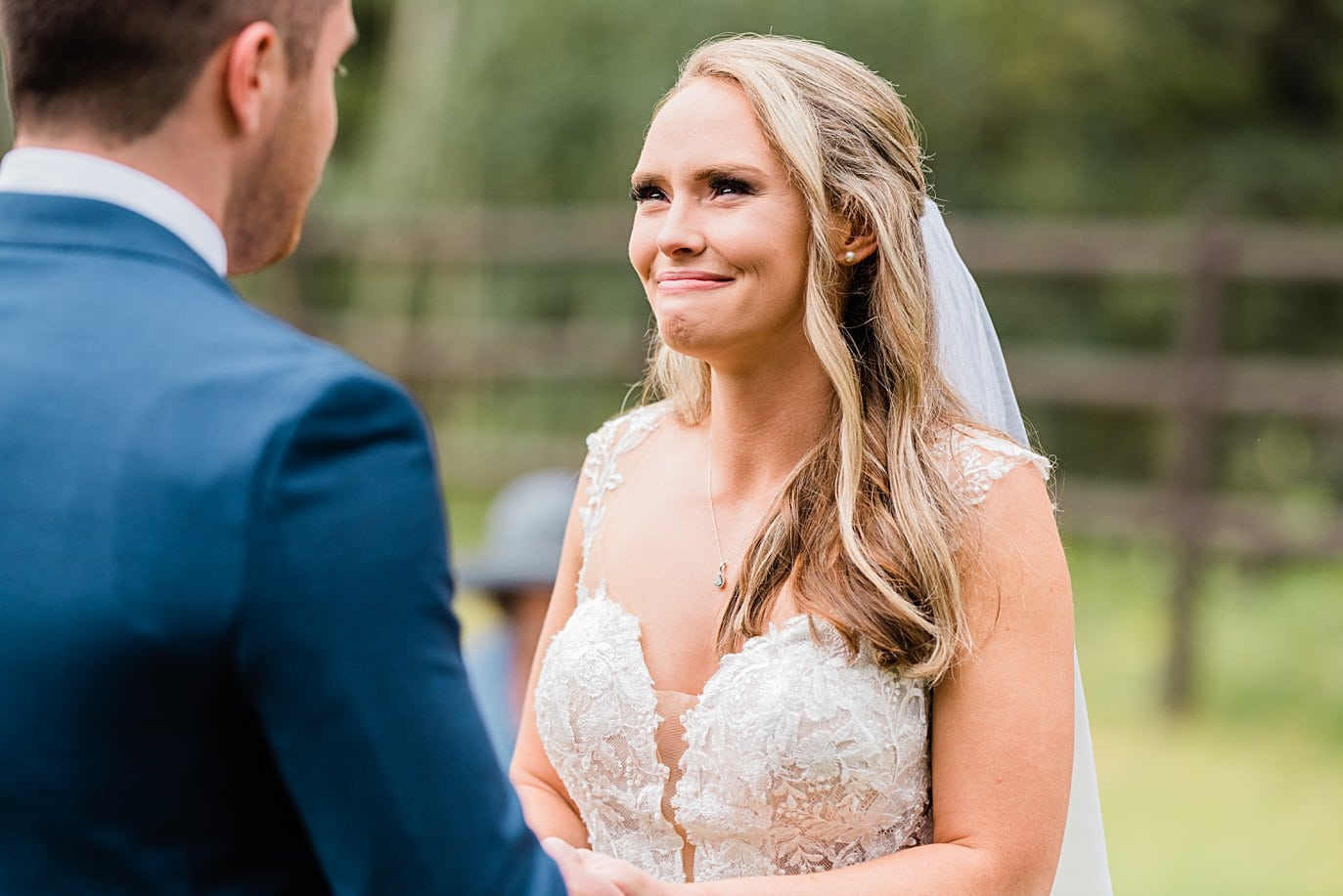 bride looks at groom with tears in her eye at Larkspur Vail Wedding by Lyons Wedding photographer Jennie Crate