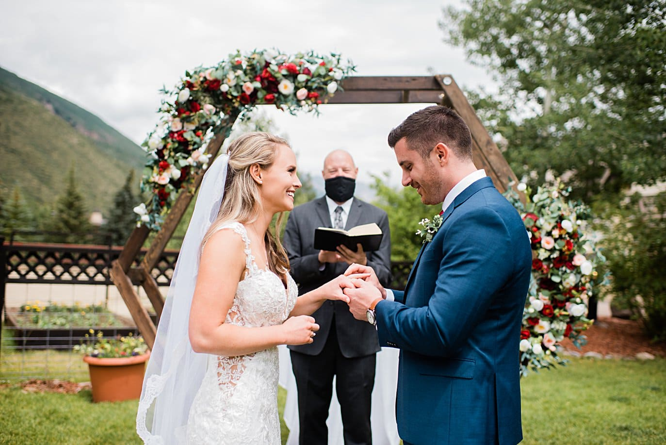 bride and groom exchange rings in front of hexagon arch at Larkspur Vail Wedding by Lyons Wedding photographer Jennie Crate