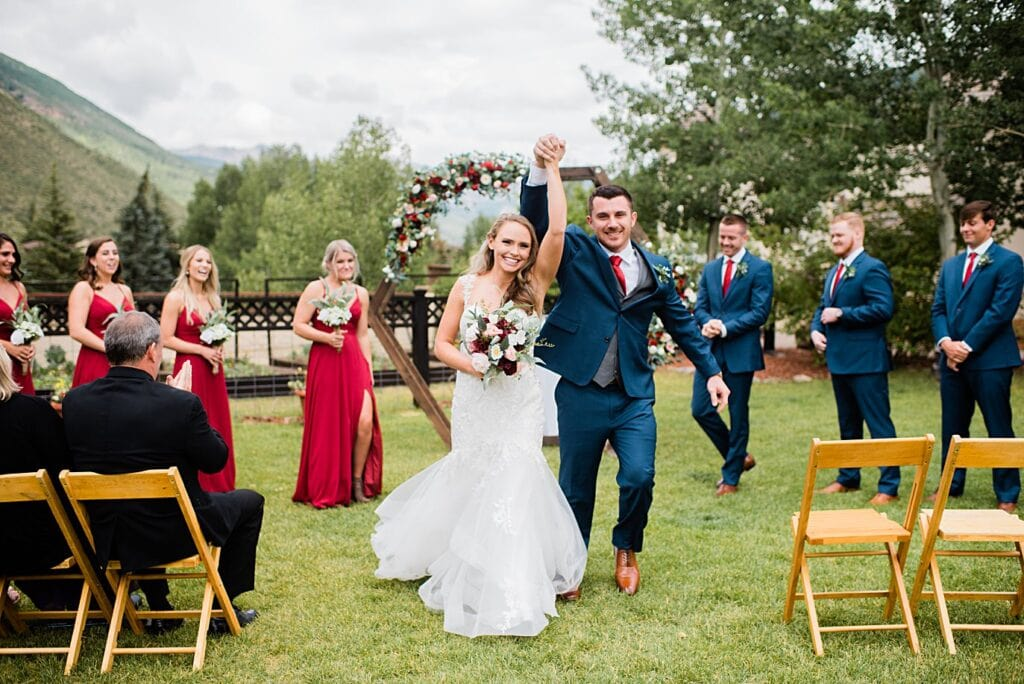 bride and groom are cheered down the aisle after wedding ceremony at Larkspur Vail Wedding by Lyons Wedding photographer Jennie Crate
