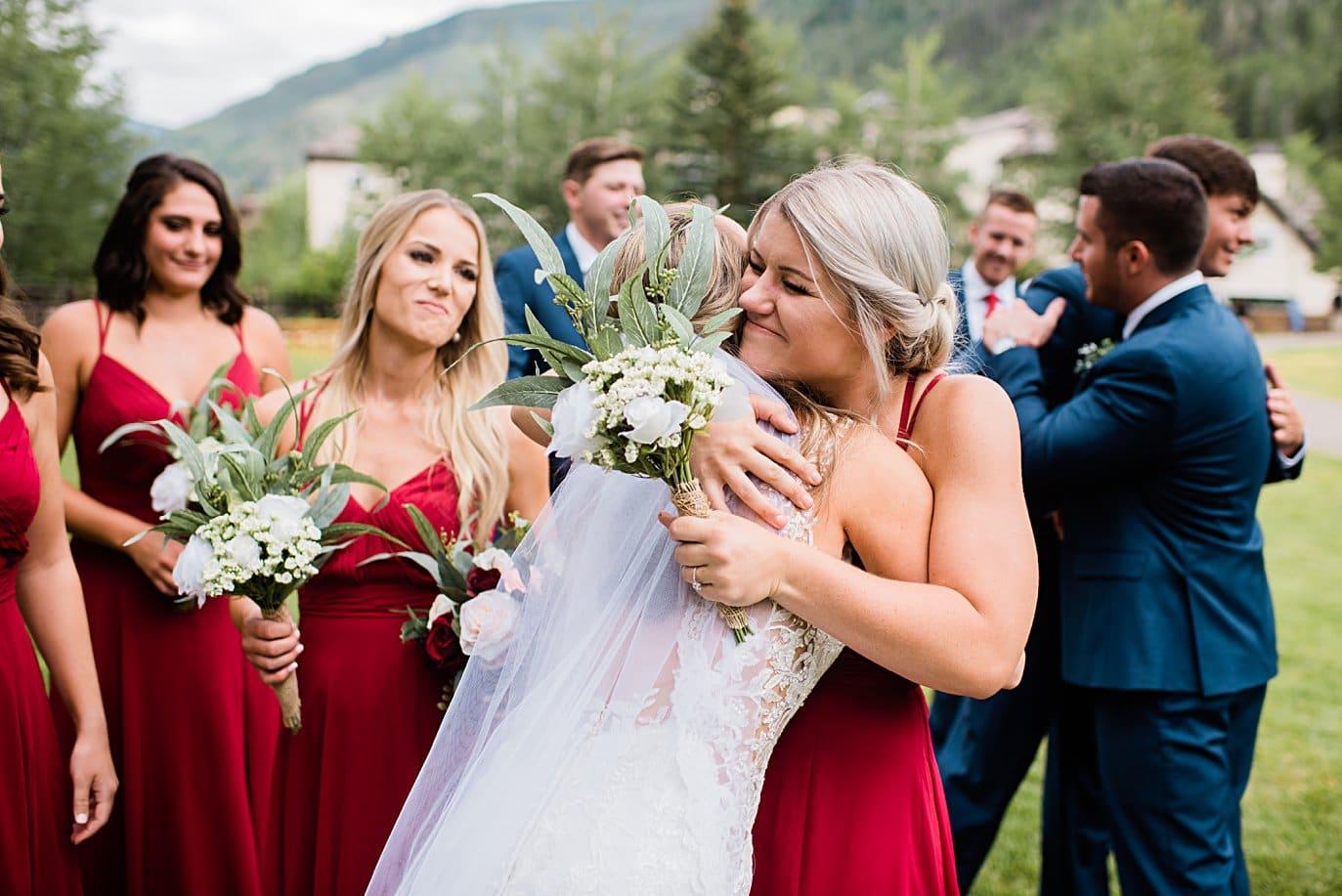 bride hugs bridesmaid at Larkspur Vail Wedding by Breckenridge Wedding photographer Jennie Crate