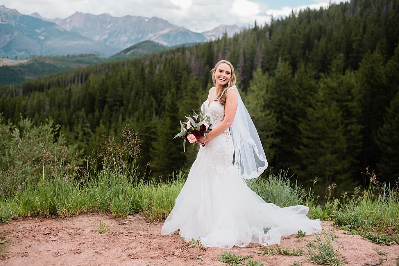 bride in sexy wedding dress and vail at top of Vail mountain at Vail Manor Lodge wedding by Breckenridge wedding photographer Jennie Crate