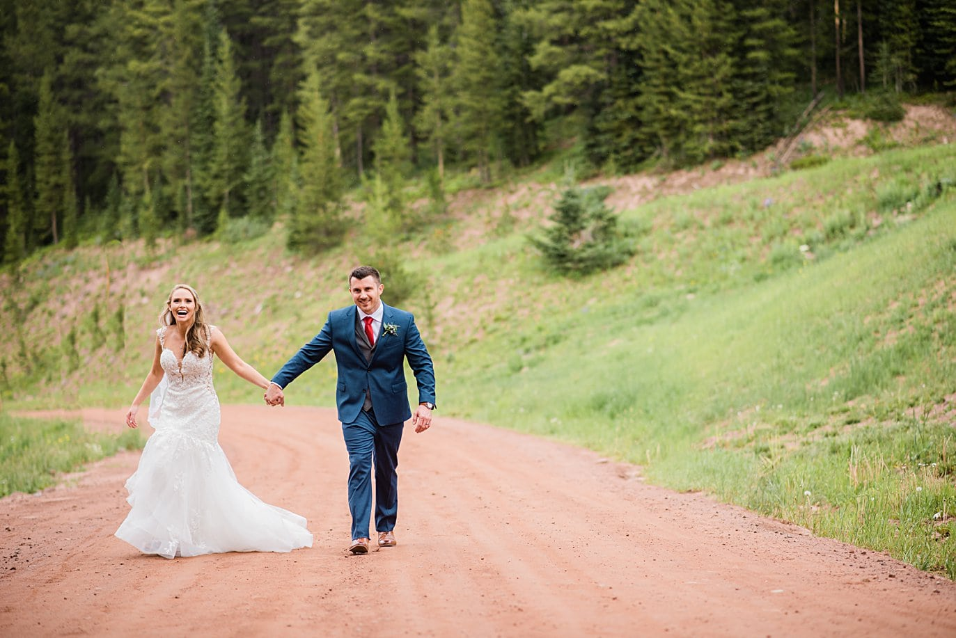 bride and groom walk down road at top of Vail mountain intimate bride and groom portrait at Vail Manor Lodge wedding by Aspen wedding photographer Jennie Crate