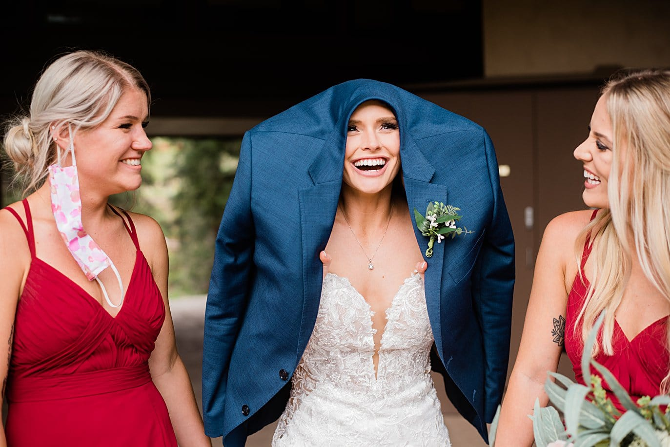Bride shelters from rain under groom's coat while bridesmaids in masks look on at Vail Manor Lodge wedding by Aspen wedding photographer Jennie Crate