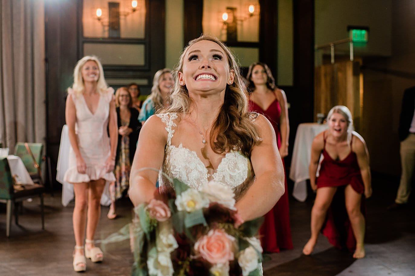 bride bouquet toss at Vail Manor Lodge wedding by Aspen wedding photographer Jennie Crate