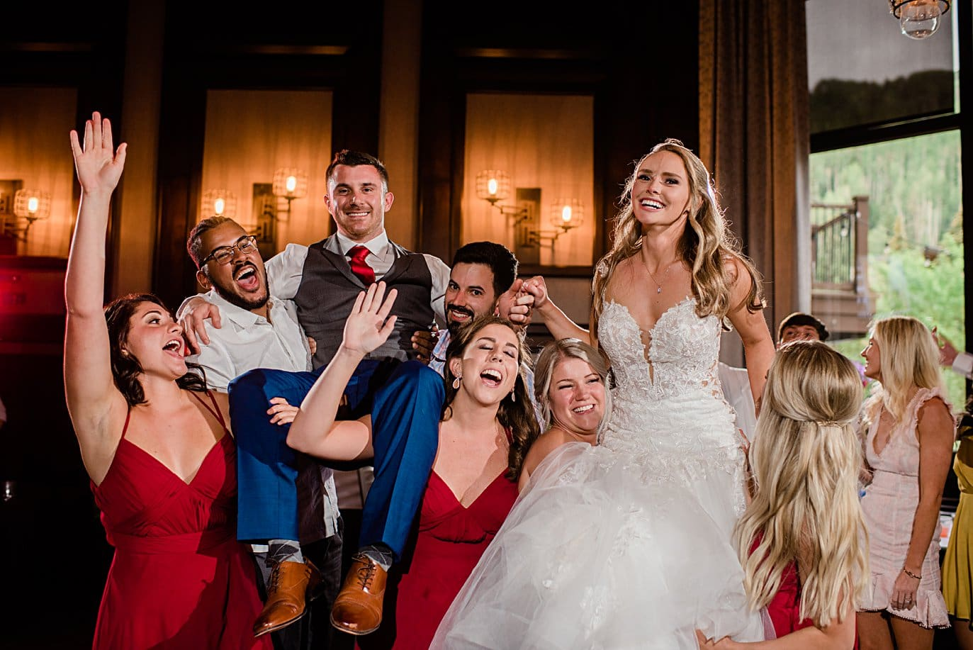 bridal party lifts bride and groom during reception at Vail Manor Lodge wedding by Aspen wedding photographer Jennie Crate
