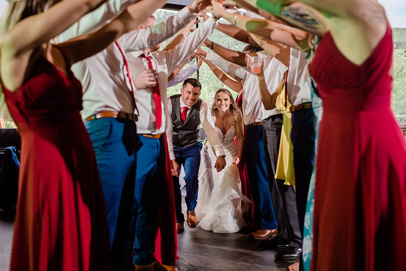 bride and groom go through tunnel at wedding reception at Vail Manor Lodge wedding by Aspen wedding photographer Jennie Crate
